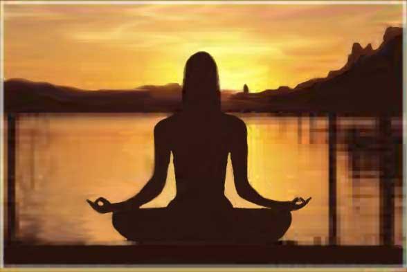 è una fotografia, la sagoma di una donna in posizione yoga, sullo sfondo l'alba
