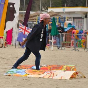 artista sulla spiaggia accanto al suo aquilone