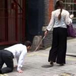Donna con uomo al guinzaglio a Londra