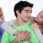 Coppia innamorata e donna gelosa sullo sfondo. Image credit: Shutterstock
