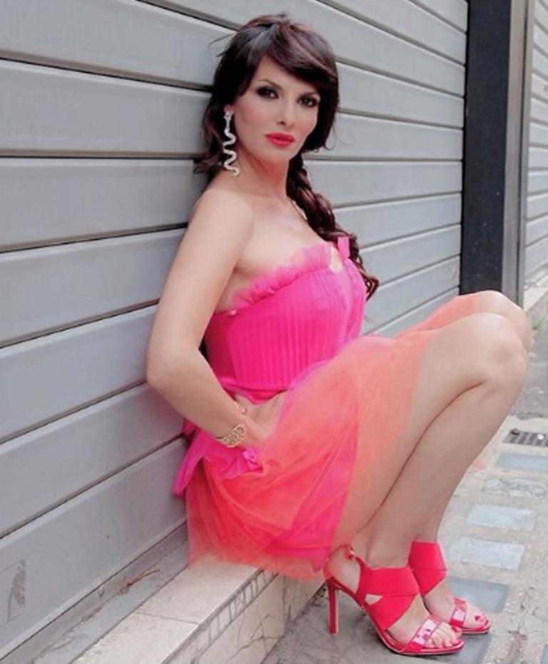 Miriana Trevisan in mini abito seduta a bordo strada