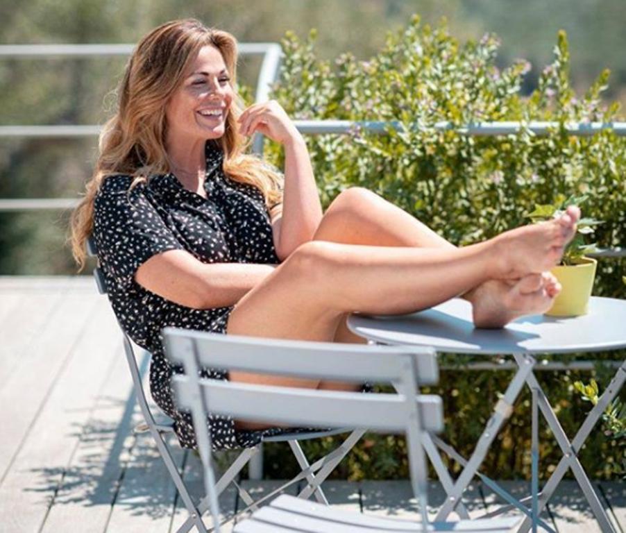 Vanessa Incontrada in mini abito con le gambe all'insù sorride alla vita